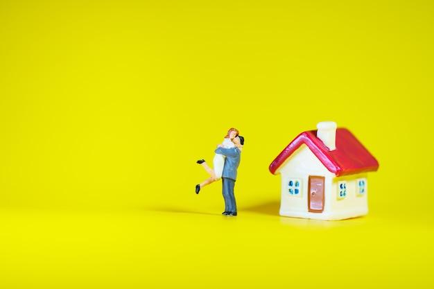 Miniatuurmensen, man en vrouw die zich met rood huis bevinden die als familie en bezitsconcept gebruiken