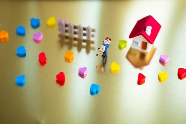 Miniatuurmensen, man omhelzingsvrouw bij minihuis die als familie en valentijnsdagconcept gebruiken