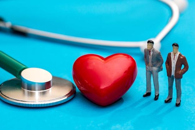 Miniatuurmensen met stethoscoop, pillen en vorm van hart die op blauw wordt geïsoleerd