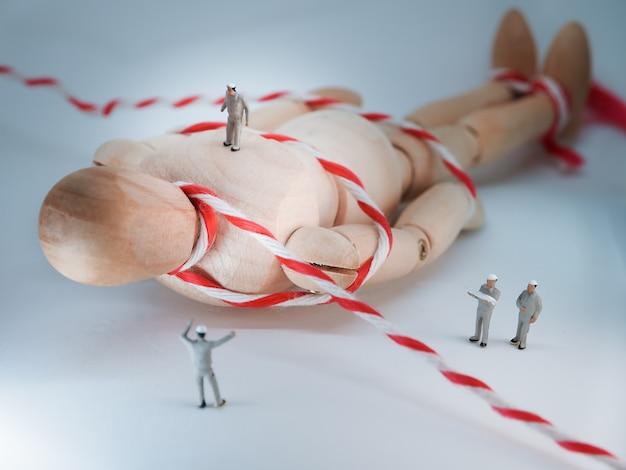 Miniatuurmensen: miniatuurwerkers hielpen met het verplaatsen van de gigantische houten pop.