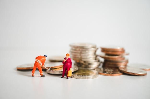 Miniatuurmensen, onderneemster die zich met arbeider op de achtergrond van stapelmuntstukken bevinden
