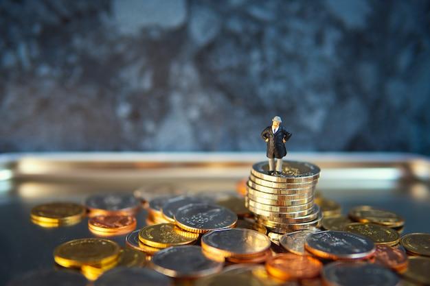 Miniatuurmensen, oude zakenman die zich op stapelmuntstukken bevinden die als zaken en financieel concept gebruiken
