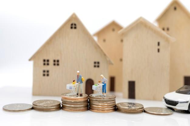 Miniatuurmensen: ouder en kinderen met winkelwagentje op muntenstapel met huis en auto. concept van winkelen in woningen en voertuigen.