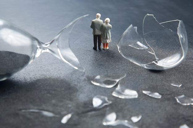 Miniatuurmensen. ouderen lopen in de buurt van de kapotte zandloper. verlies van levensduur. crisis van hoop en problemen van ouderdom