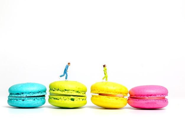 Miniatuurmensen, paar dat op kleurrijke franse makaron loopt,