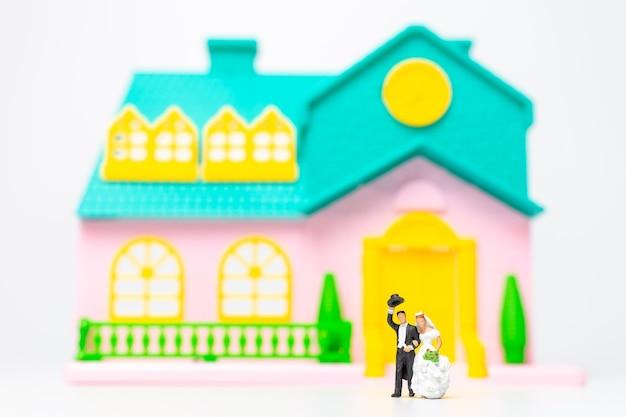 Miniatuurmensen, paar dat zich voor hun huis samen bevindt