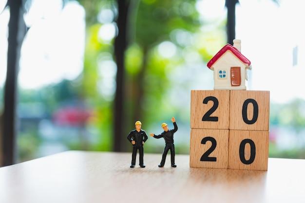 Miniatuurmensen, paarspecialist die zich met minihuis en houten blokjaar 2020 bevinden die als concept van onroerende goederenbezit gebruiken
