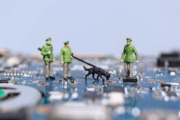 Miniatuurmensen, politie en detective werken aan een computermoederbord, concept van cybercriminaliteit Premium Foto