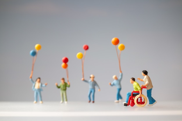 Miniatuurmensen positieve familie die voor hun gehandicapte vader zorgt