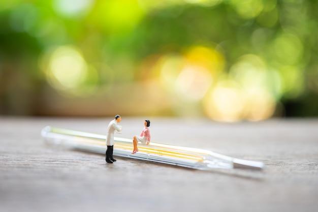 Miniatuurmensen raadpleeg een arts om gezondheidsproblemen te vragen