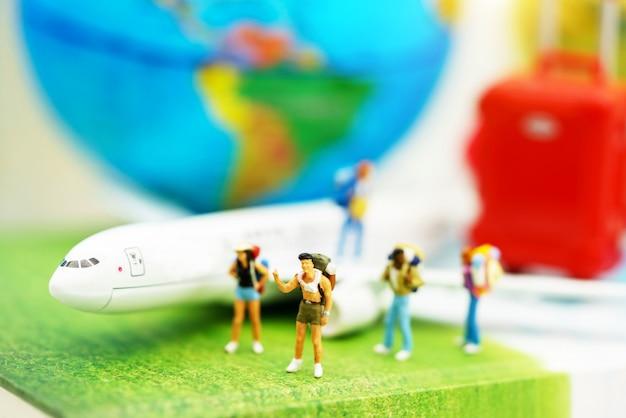 Miniatuurmensen: reiziger met rugzak die op het pad van toerisme per vliegtuig lopen.