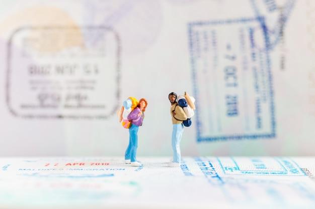 Miniatuurmensen: reiziger met rugzak die op paspoort loopt