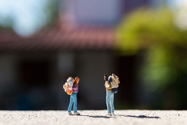 Miniatuurmensen: reiziger met rugzak die zich op de weg bevinden
