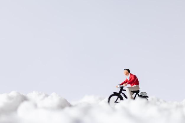 Miniatuurmensen: reizigers die fietsen op sneeuw