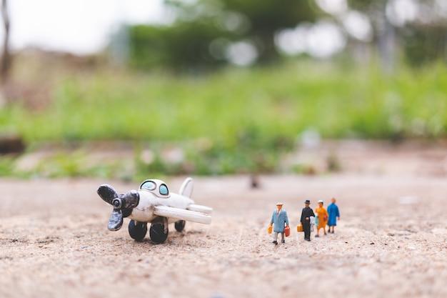 Miniatuurmensen: reizigers die handbagage vasthouden, stappen in het vliegtuig