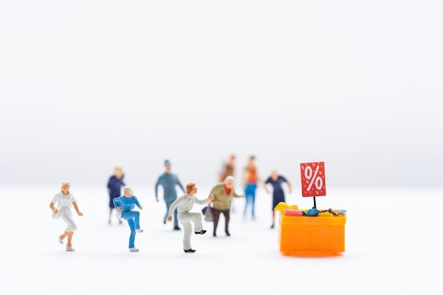 Miniatuurmensen, shoppers die naar een kortingsvak rennen om te winkelen met korting op artikelen