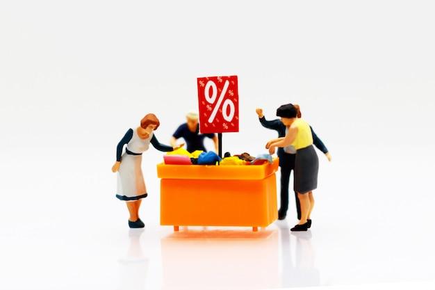 Miniatuurmensen: shoppers kopen te koop aangeboden artikelen met kortingsplateau.