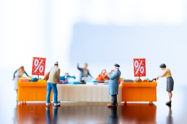 Miniatuurmensen, shoppers met kortingsbakje voor het kopen van afgeprijsde artikelen
