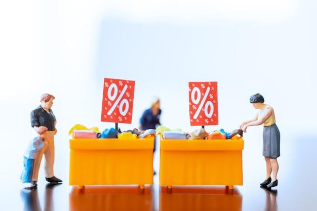 Miniatuurmensen, shoppers met kortingsbakje voor het kopen van afgeprijsde artikelen Premium Foto