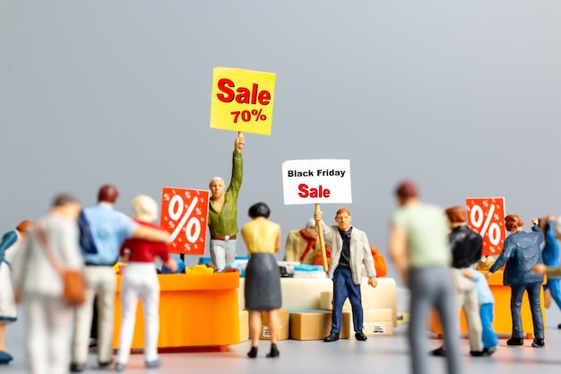 Miniatuurmensen, shoppers met kortingslade om afgeprijsde artikelen te winkelen, black friday-concept