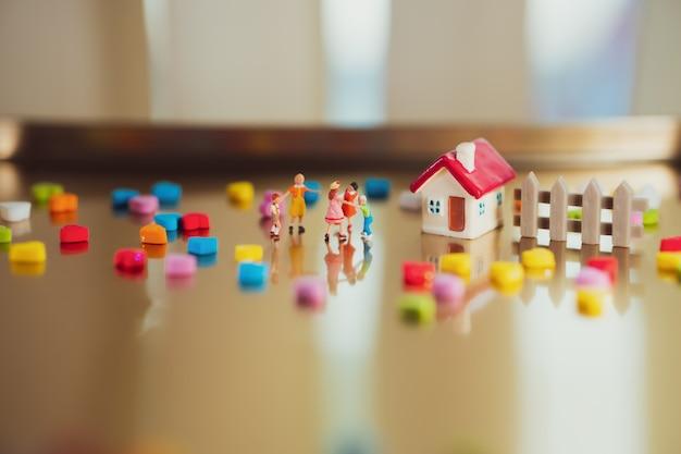 Miniatuurmensen, spelende kinderen die thuis als familie en onderwijsconcept gebruiken
