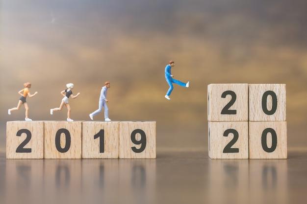 Miniatuurmensen springen van nummer 2019 naar 2020