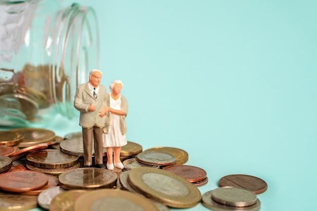 Miniatuurmensen staan op munten ouderen en hun spaarpensioen