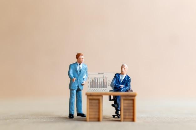 Miniatuurmensen uit het bedrijfsleven die naar analistengrafiek kijken op de schermachtergrond, bedrijfsconcept.