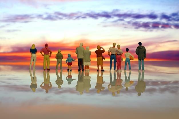 Miniatuurmensen van verschillende leeftijden kijken naar de zonsondergang aan het strand