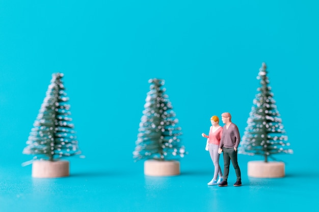 Miniatuurmensen, verliefde paar die naast een kerstboom staan, kerstmis en gelukkig nieuwjaar concept.