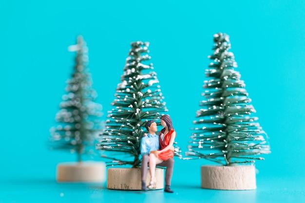 Miniatuurmensen, verliefde paar zittend naast een kerstboom, kerstmis en gelukkig nieuwjaar concept.
