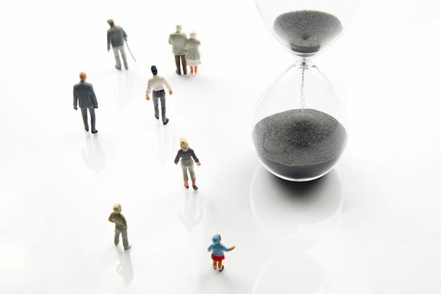 Miniatuurmensen. verschillende mensen lopen naast de zandloper. levensduur van de mensheid