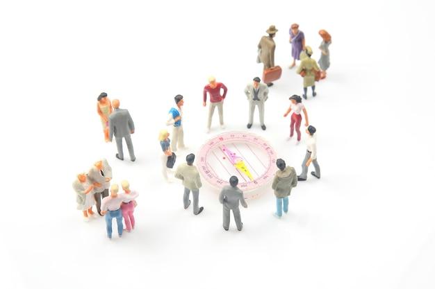 Miniatuurmensen. verschillende mensen staan bij het kompas. richting vinden in het leven