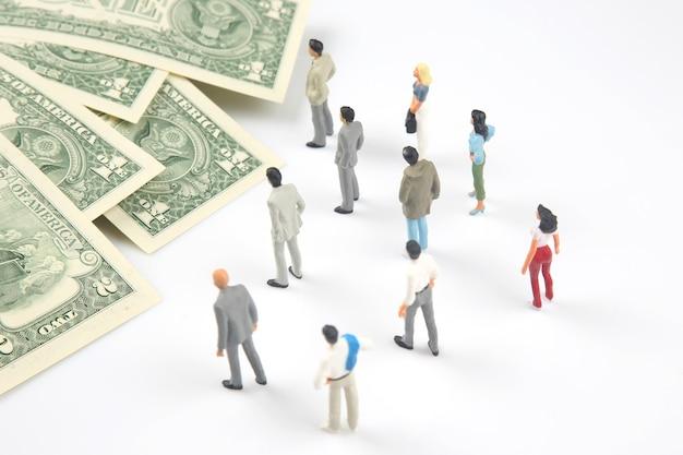 Miniatuurmensen. verschillende mensen staan in de buurt van dollargeld. investeringen en inkomsten voor werk