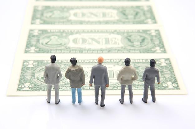 Miniatuurmensen. verschillende zakenman staat in de buurt van dollargeld. investeringen en inkomsten voor werk