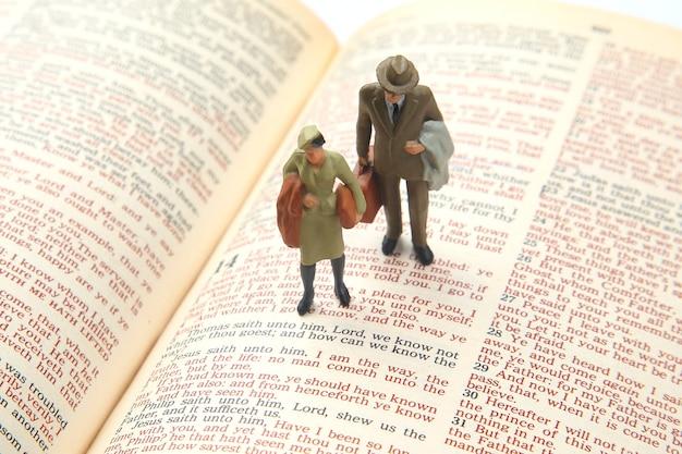 Miniatuurmensen. vrouw en man staan op de bijbeltekst. zoek naar het pad van het leven. ik ben de weg.