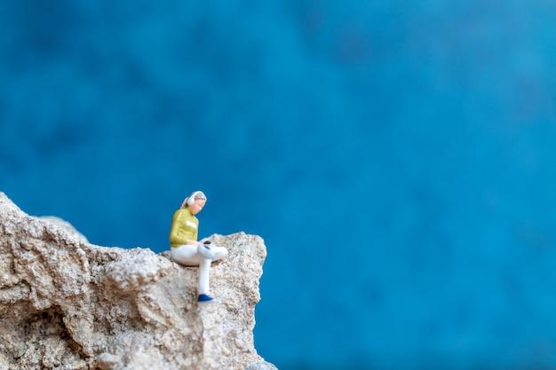 Miniatuurmensen vrouw met koptelefoon en luisteren naar muziek op smartphone zittend op de rots
