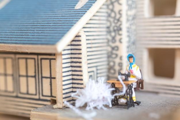 Miniatuurmensen vrouw naaien op een naaimachine bij haar thuis. vrouwelijke naaisters werken aan de naaimachine
