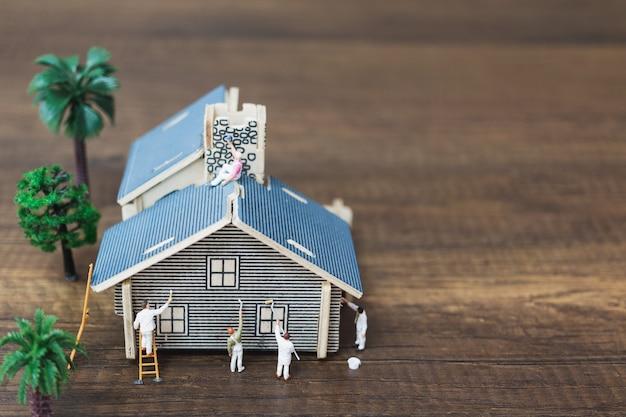 Miniatuurmensen: werkersteam dat een nieuw huis schildert.