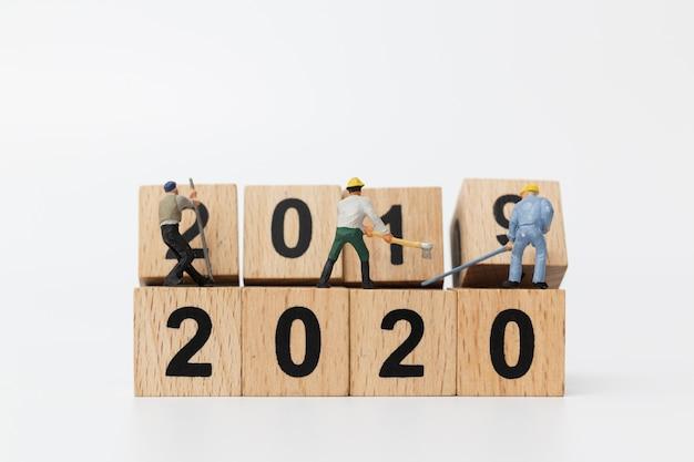 Miniatuurmensen: werkersteam maakt houten blok nummer 2020