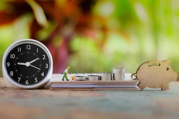 Miniatuurmensen: werknemer munten stapel op boek met klok en houten varken.