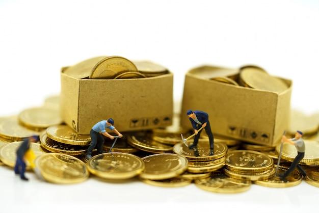 Miniatuurmensen: werknemers die werken aan gouden munten met dozen. financiën concept.