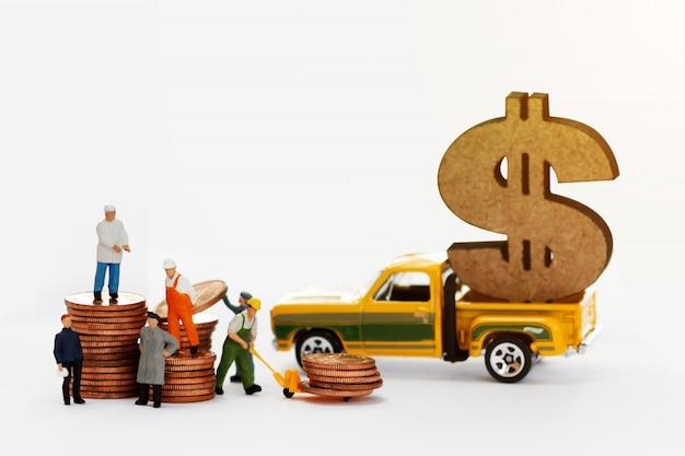 Miniatuurmensen: werknemers verplaatsen stapel munten naar pick-up truck.