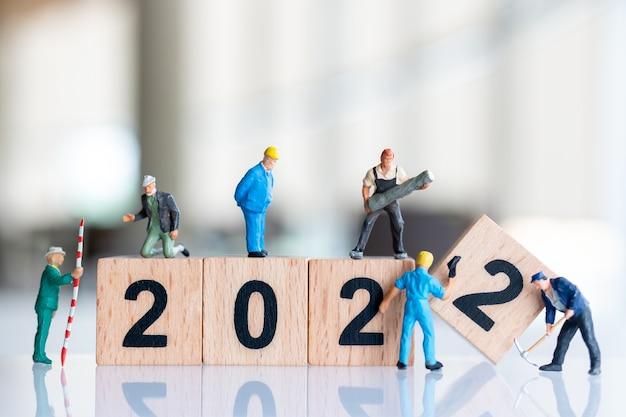 Miniatuurmensen: werknemersteam maakt houten bloknummer 2022, gelukkig nieuwjaarsconcept