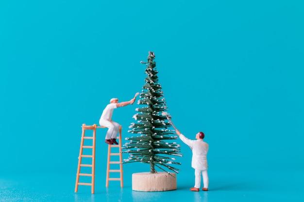 Miniatuurmensen, werknemersteam schilderen op kerstboom, kerstmis en gelukkig nieuwjaar concept.
