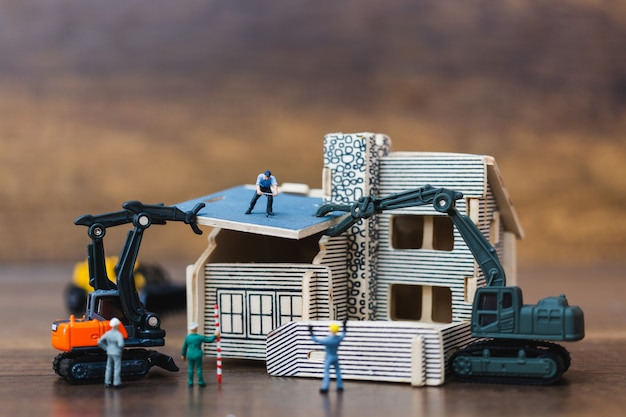 Miniatuurmensen: werkteam voor het bouwen van een huis