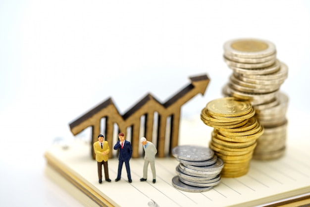 Miniatuurmensen: zakenlieden die zich op muntstukkenstapel bevinden met houten grafiek.