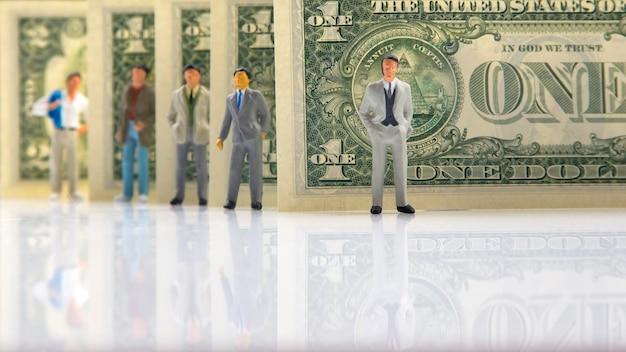 Miniatuurmensen. zakenlieden staan in de buurt van dollargeld. ondernemer bedrijfsconcept