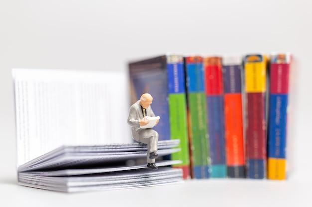 Miniatuurmensen: zakenman die de krant leest en op een boek zit, kennisconcept Premium Foto