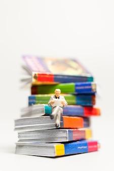 Miniatuurmensen: zakenman die de krant leest en op een boek zit, kennisconcept